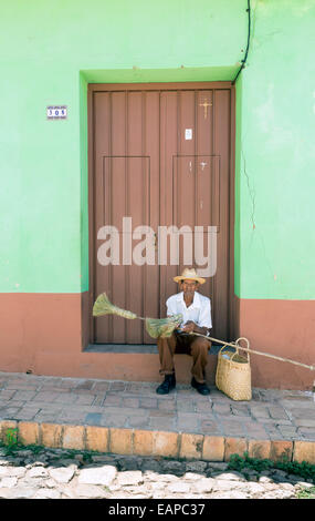 TRINIDAD, CUBA - MAY 8, 2014: An old broom street vendor seated at the door of a house - Stock Photo