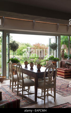 Roundback wooden dining chairs around antique farmhouse table in dining room with open french windows leading out - Stock Photo