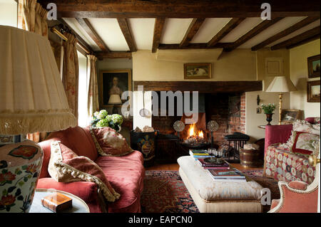 Inglenook fireplace in cosy sitting room with original beamed ceiling and red sofa - Stock Photo