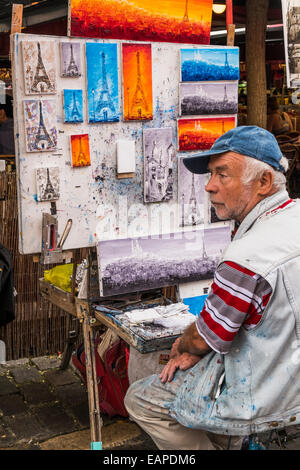 street painter at place du tertre in the montmartre district, to his left various paintings showing the eiffel tower, - Stock Photo