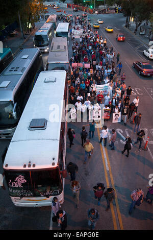 Caravan for Ayotzinapa and demonstrators hold posters and placards during a march in protest for the disappearance - Stock Photo