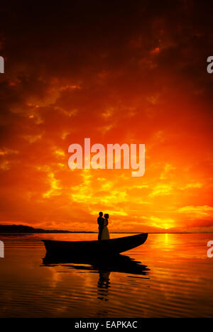 Silhouette of a couple in boat on river in sunset, beautiful skyes - Stock Photo