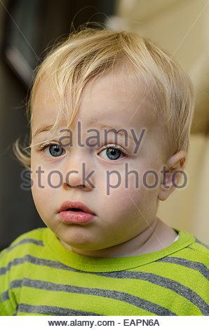 portrait of a blond blue-eyed 18-month old boy wearing a stripy jumper - Stock Photo