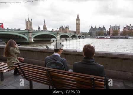 Two business men in suits and one female tourist sit on benches on next to the River Thames, opposite the Palace - Stock Photo