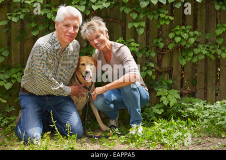 Elderly man and smiling woman sitting with their dog in a garden - Stock Photo