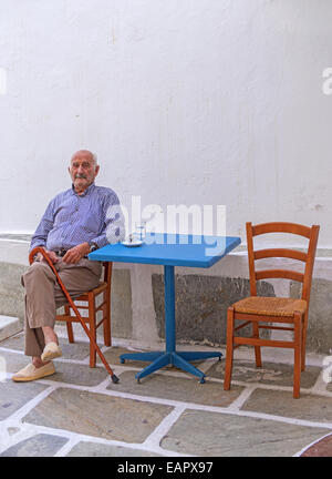 A local veteran of life drinking Greek coffee at the frontage of a kafeneio (café) in Chora village, Ios island, - Stock Photo
