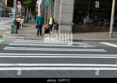 People waiting on a green light to cross a street in Seattle, Washington - Stock Photo