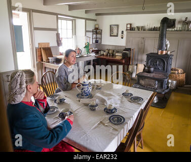 Drinking Tea in the Kitchen. Two women drink tea at the kitchen table. A large wood stove and a water pump are in - Stock Photo