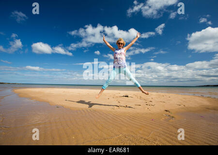 A teeneage girl on a sandy island being cut off by the incoming tide at Low Newton, Northumberland, UK. - Stock Photo