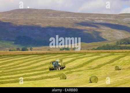 Tractor and trailer transporting hay bails below radar station. Great Dun Fell, Eden Valley, Cumbria, England, UK. - Stock Photo