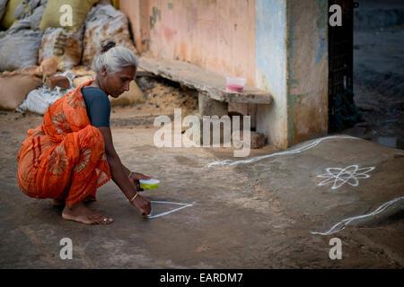 Elderly woman creating a traditional Rangoli, Kolam or Muggu, decorative pattern made of coloured sand, outside - Stock Photo