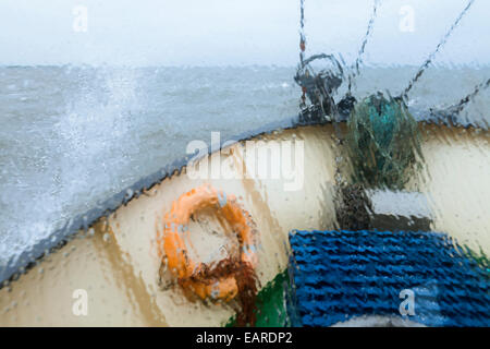 View through the wet window of the bow of the shrimp boat 'Columbus' from Pellworm island, travelling in North Frisian - Stock Photo