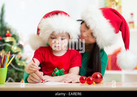 Child girl and mom writing christmas letter to Santa - Stock Photo