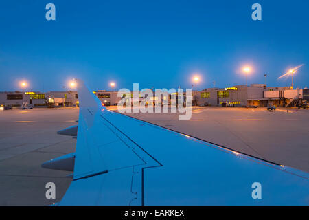 Looking Out Airplane Window As Plane Approaches Airport Gate - Stock Photo