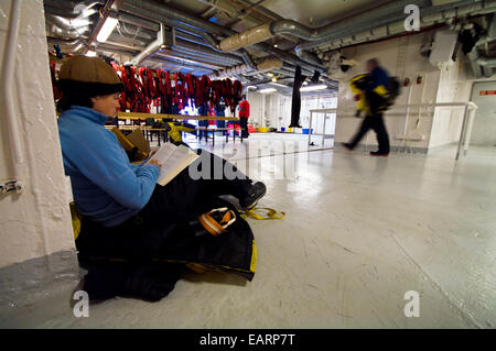 An Antarctic ship's ornithologist reading and resting in the hold. - Stock Photo