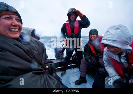 Tourists enjoy wild weather and rough seas in a zodiac in Antarctica. - Stock Photo
