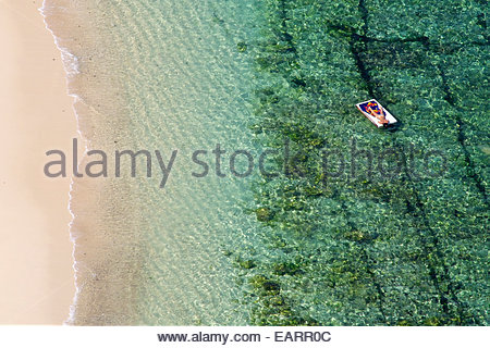 A lone sunbather relaxes on a floating bed, by the beach. - Stock Photo