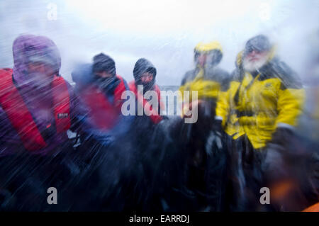 Ship's crew and tourists shower in icy sea water on a rough ocean. - Stock Photo