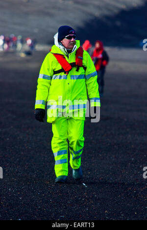 A tourist in fluorescent alpine clothing hiking on a volcanic beach. - Stock Photo