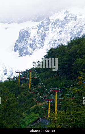 An alpine chairlift rises through a beech forest to a ski resort. - Stock Photo