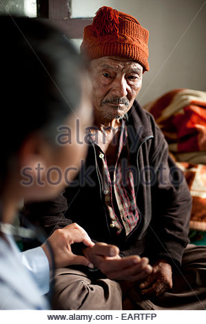 An older man has his pulse checked by a nurse in a rural hospital. - Stock Photo