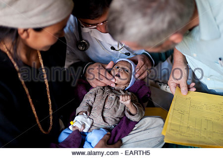 Doctors check a small baby who is suffering from pneumonia. - Stock Photo
