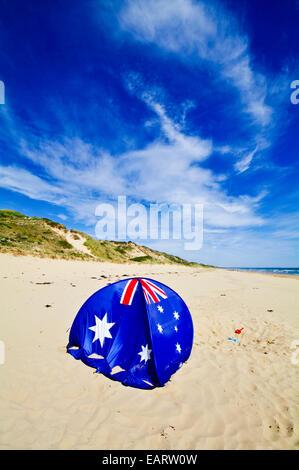 An Australian flag beach dome for shade on a sunny beach. - Stock Photo