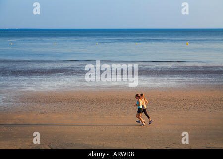 Two women joggers running on the hard sand of low tide on the beach - Stock Photo