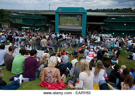 Tennis fans gather on Henman Hill to watch Wimbledon on a big television screen. - Stock Photo