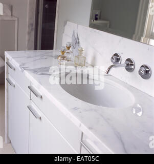 Washbasin set in marble top on cupboard unit - Stock Photo