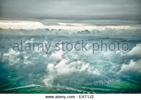 An aerial view of Karst formations through dense cloud cover. - Stock Photo