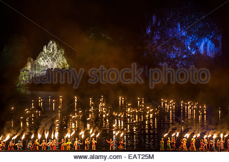 Men and women holding torches perform in the Liu Sanjie light show. - Stock Photo