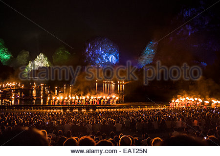 Audience members watching the light show, in an outdoor theater. - Stock Photo