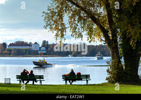 Couple sitting on a bench seat watching a Chiemsee Taxi Boat pass by, Fraueninsel, Chiemsee, Chiemgau, Upper Bavaria, - Stock Photo