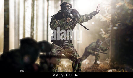 Paintball team in action rainy forest location - Stock Photo
