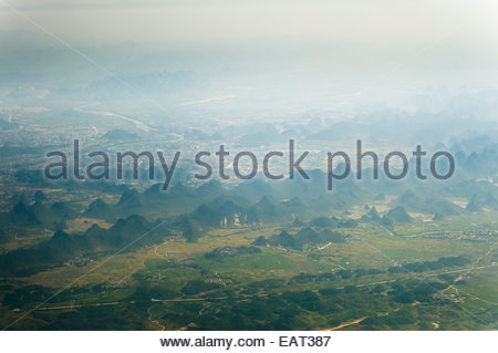 Aerial view of karst formations near Guilin through fog. - Stock Photo