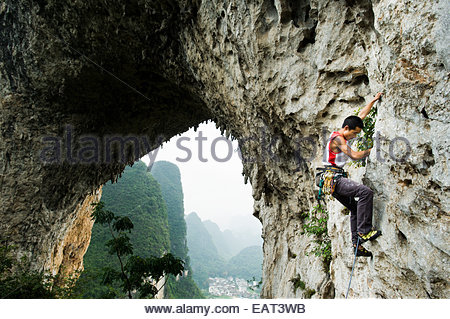 A man rock climbs on Moon Hill near Yangshuo. - Stock Photo