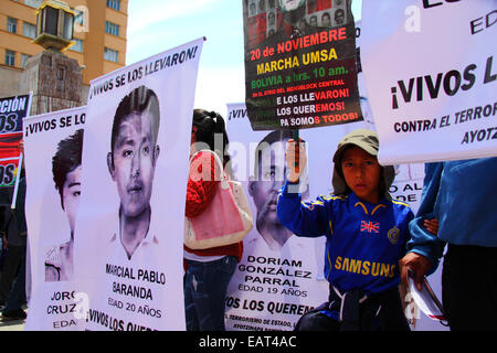 La Paz, Bolivia. 20th November, 2014. A young boy stands next to banners with photos of the 43 missing students - Stock Photo