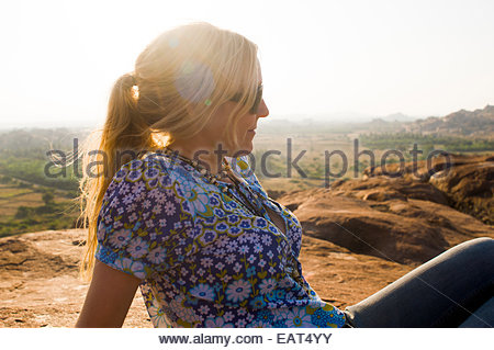 A girl relaxes in the sun on the boulders surrounding Hampi - Stock Photo