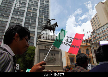 La Paz, Bolivia. 20th November, 2014. A protester holding a Mexican flag with 43 Ayotzinapa on it passes a statue - Stock Photo
