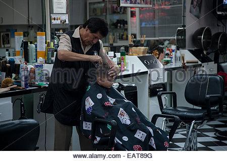A boy gets his hair cut at a barber shop in Little havana. - Stock Photo