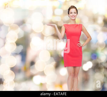 smiling young woman in dress holding something - Stock Photo