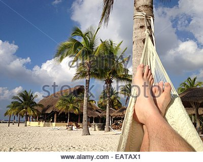 Relaxing in a hammock on the beach in Cozumel. - Stock Photo