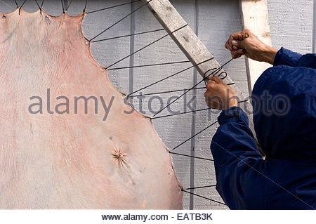 A local stretches seal skin to dry. - Stock Photo