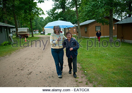 An adult mother and daughter take a walk in the rain. - Stock Photo