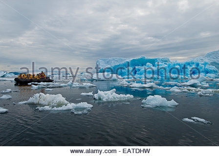 Tourists in a rubber raft cruising through a field of icebergs. - Stock Photo