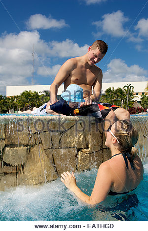 A mother and father play with their son in a resort swimming pool. - Stock Photo