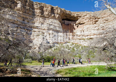 A school group below the Sinagua cliff dwelling from around 1100 AD. - Stock Photo