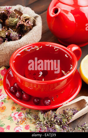 red tea cup and teapot, healing herbs and lemon on kitchen table - Stock Photo