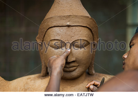 A man sculpts a Buddha from clay which will eventually be bronzed. - Stock Photo